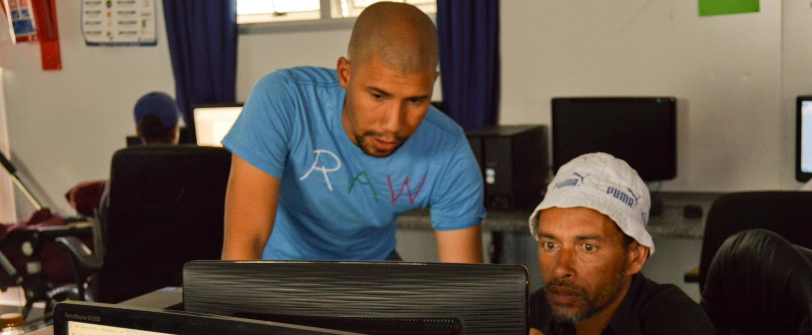 Voluntario ayudando a un estudiante de informática en Sudáfrica.